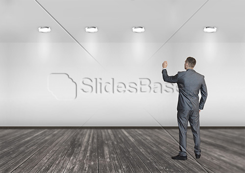 businessman-writing-business-plan-to-wall-empty-room-office-stock-photo